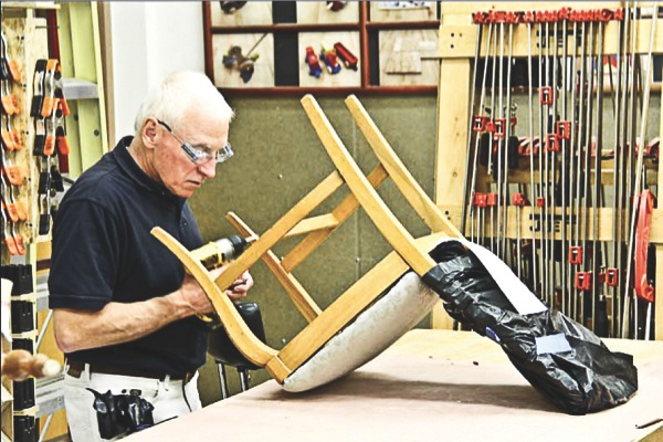 Jim Jessup assembles a chair after tightening the legs. (Photo provided)