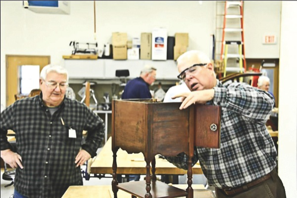 Gerry Macozzi and John Sterling work on a tobacco cabinet to reattach the top. (Photo provided)