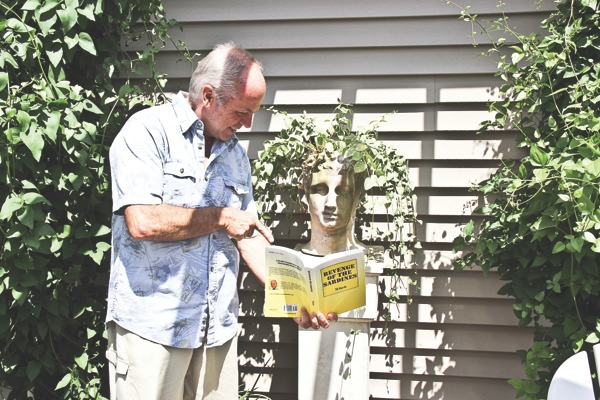 Author and columnist T.R. Kerth points out a section of his new book to a stone head at his Sun City home. The scene is a perfect depiction of Kerth's humor. (Photos by Hannah Sturtecky/Sun Day)
