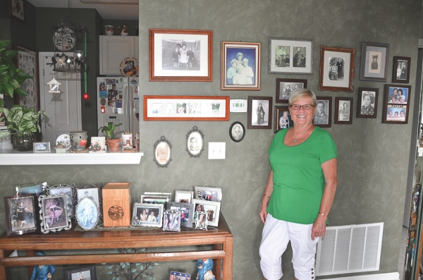 Margitta (Kitty) Rizzo stands before her family gallery wall in her home. (Photo provided)